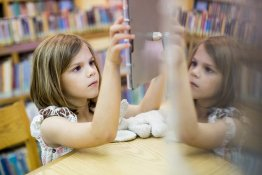 A child uses an digital tablet affixed to a table at the library