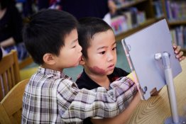Two young children use a digital tablet affixed to a wooden table