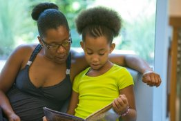 An adult and child read a book together.