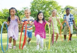Five children holding hoola hoops in a field