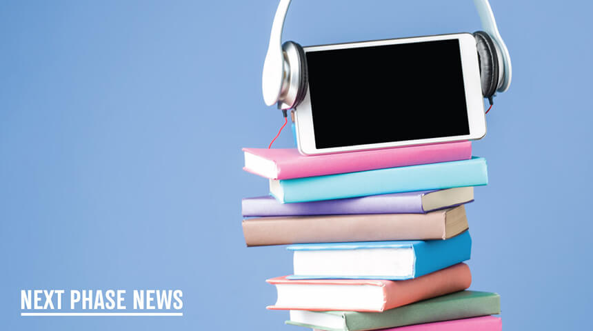 tablet and headphones on top of a stack of books