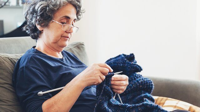 An older woman knitting a blue scarf