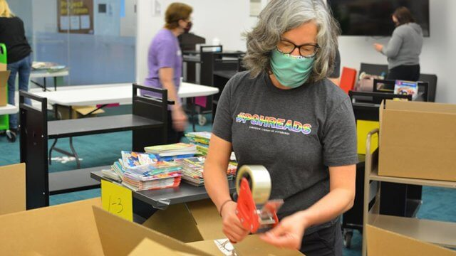 Librarian wearing #PGHREADS t-shirt packing a box of children's books to be distributed at Summer Reading book drop locations around Pittsburgh.