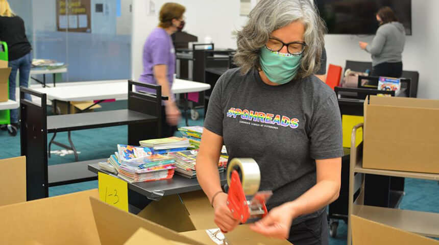 librarian wearing #PGHREADS tshirt packs a box of children's books to be distributed at Summer Reading book drop locations around Pittsburgh