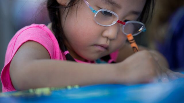 A child wearing glasses colors coloring with an orange crayon.