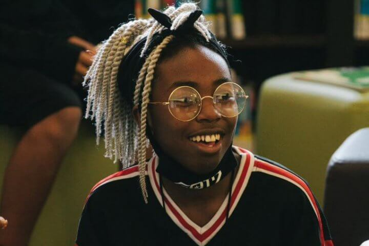 A smiling teen in glasses and a sporty sweater