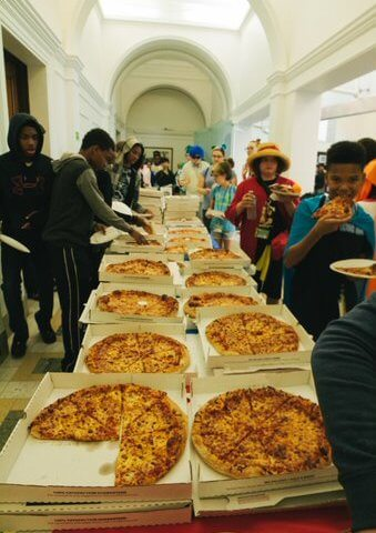 Rows of pizza and pizza-eating teens line a table at the Library.