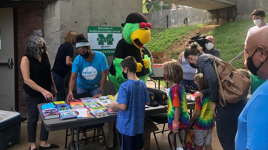 Librarians and Pirate Parrot mascot distribue books to kids at a Pittsburgh park