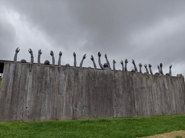 A photograph of a tall concrete wall with 10 pairs of arms streching upward behind it.