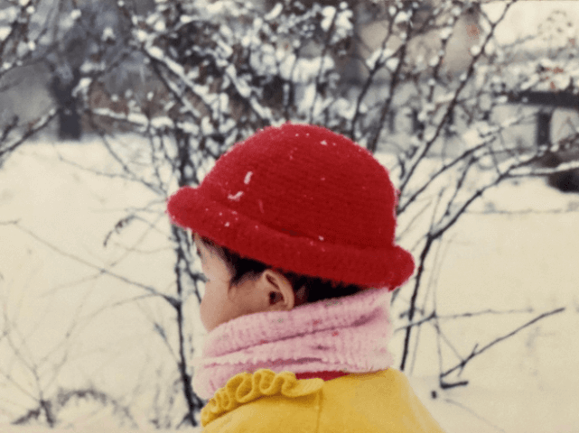 A photograph of a young girl wearing a red winter hat, a pink scarf and a yellow coat. There is a snowy background and she is turned away from the viewer.