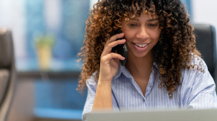 Photo of a Black woman with long hair talking on a phone while looking at a laptop screen and smiling