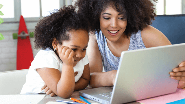 A smiling adult and child look at a laptop together.