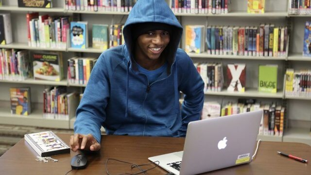 A smiling teen wearing a blue hoodie uses a laptop in front of a shelf of comic books