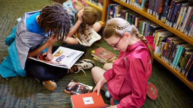 Three tweens sit on the floor of the library in front of a bookshelf, each reading a book