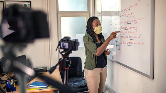A teacher wearing a face mask writes on a white board in a classroom while being filmed.