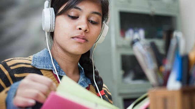 Teen wearing headphones and reading a book
