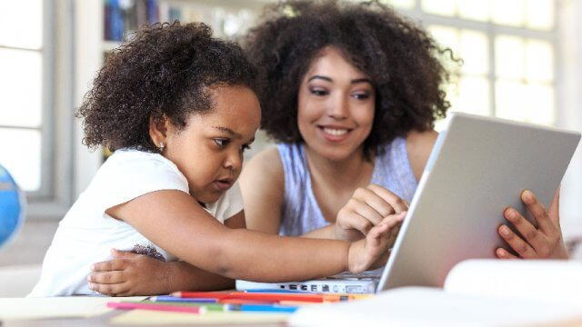 Parent and child looking at a laptop computer together