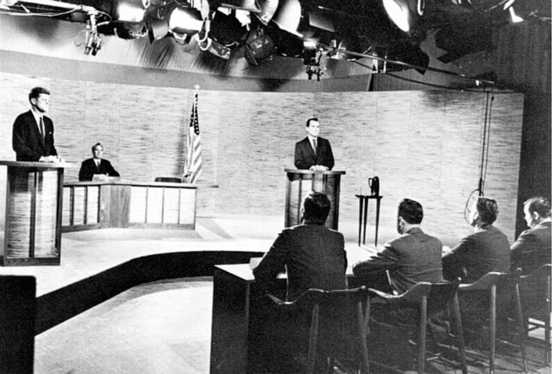four people and a moderator watch John F Kennedy and Richard Nixon debate in a television studio