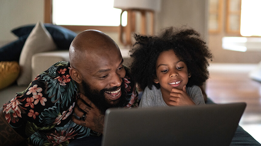 Photo of an adult and young child smiling while looking at a laptop computer.