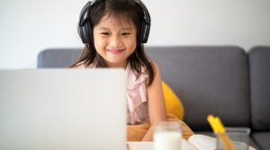 Young child wearing headphones smiles at her computer during virtual learning