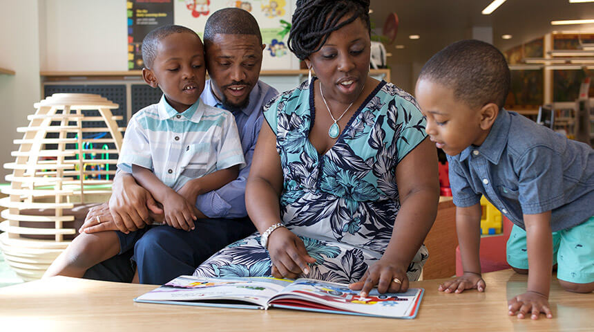 A family comprised of a mother, father and two young boys read a book together in the Children's section of the library.