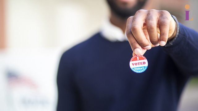 "Adult wearing a blue sweater holds an ""I voted"" sticker in their hand"