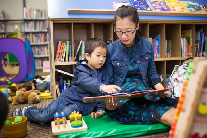 An adult and school-age child read together in the childre;n section of the library surrounded by toys and games