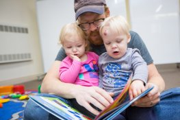 An adult and two toddlers read a book together.