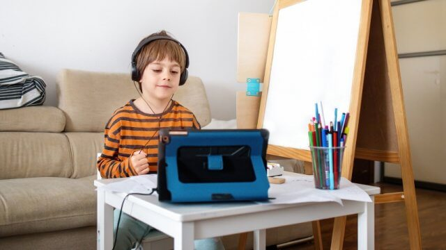 Young boy wearing headphones and looking at tablet with markers, pencils and an easel nearby