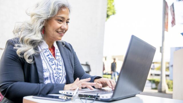 Older woman smiling and typing on a laptop