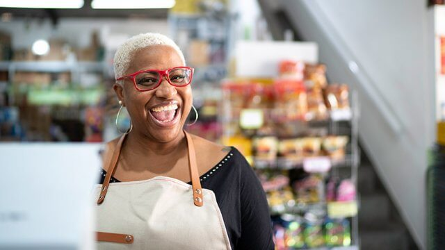 Smiling person wearing an apron in a store