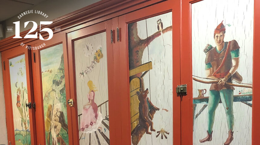 Illustrations of folk and fairy tale characters on cupboards with the library's 125 anniversary insignia.
