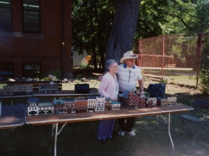 man and woman standing next to table filled with miniature buildings