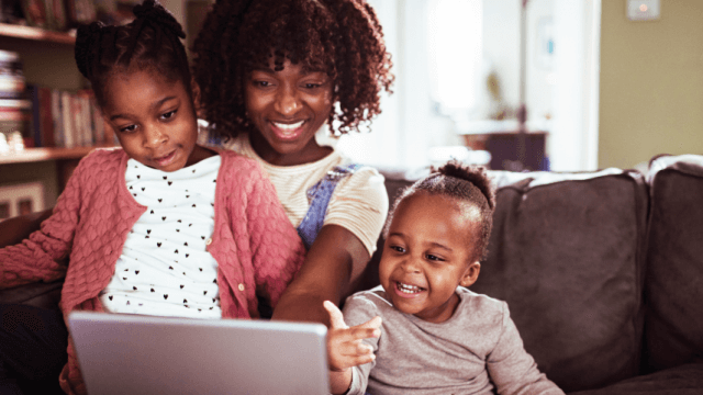 A parent and two children use a laptop together at home.