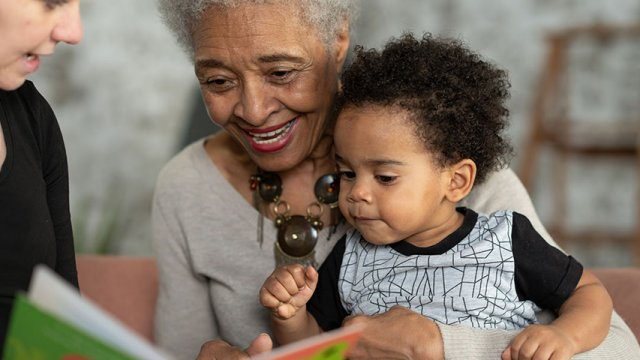 An older woman holds a baby while looking at a book
