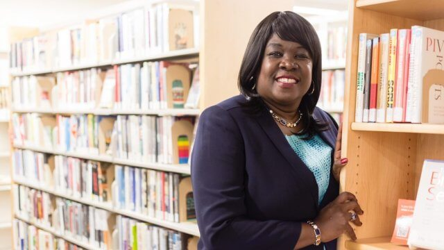 Person leaning against library book shelf in business attire.