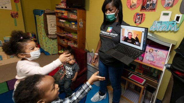 A teacher holds a laptop displaying a CLP virtual storytime to a group of young children