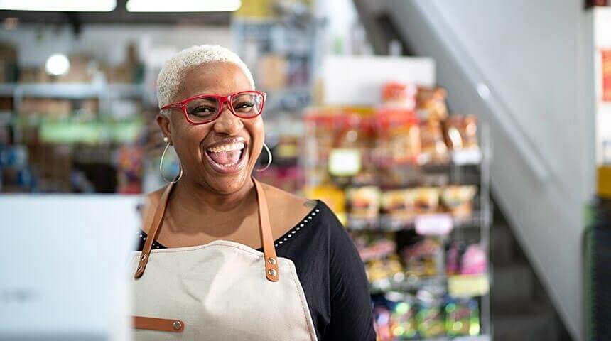 Smiling person wearing an apron in a store.