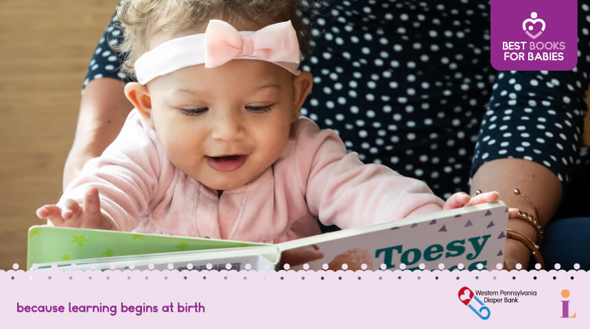 Smiling baby wearing a headband looking at a board book
