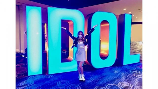 """Teen girl in white dress and face mask stand in front of a glowing """"American Idol"""" sign"""