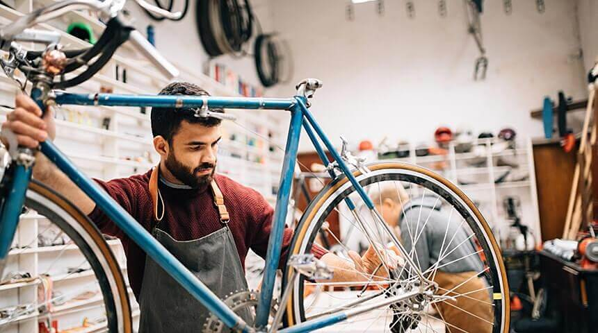Person wearing apron fixing a bicycle at their work bench.