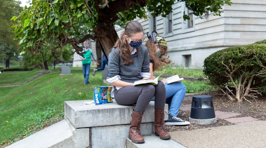 Teen girl wearing a blue face mask reading a book on the CLP-Main front steps