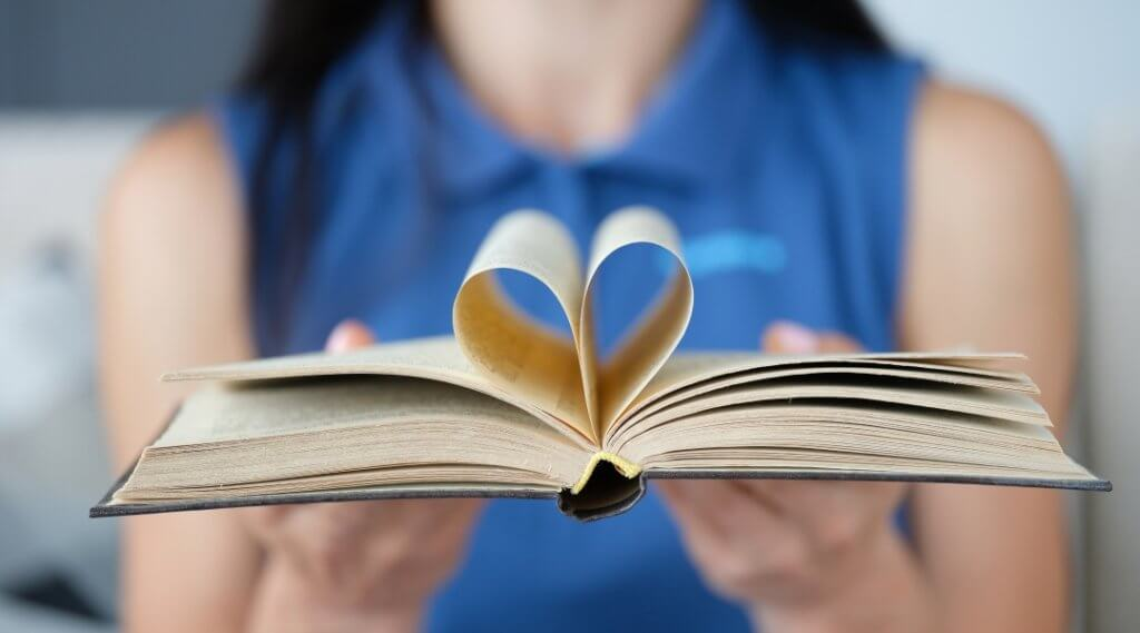 Person in blue shirt presenting a hardcover books with pages bent toward the spine to look like a heart