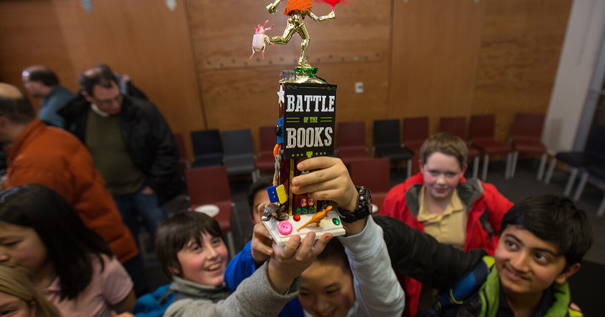 """A group of middle school-aged kids holding up a Carnegie Library of Pittsburgh """"Battle of the Books"""" trophy"""