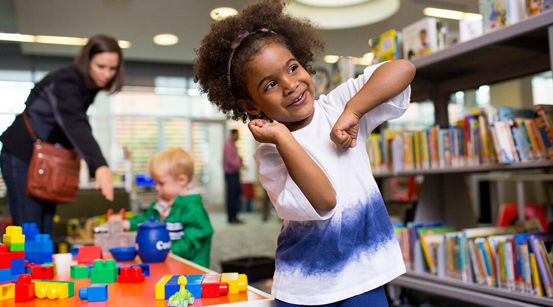 Little girl dancing next to toys in Children's Department