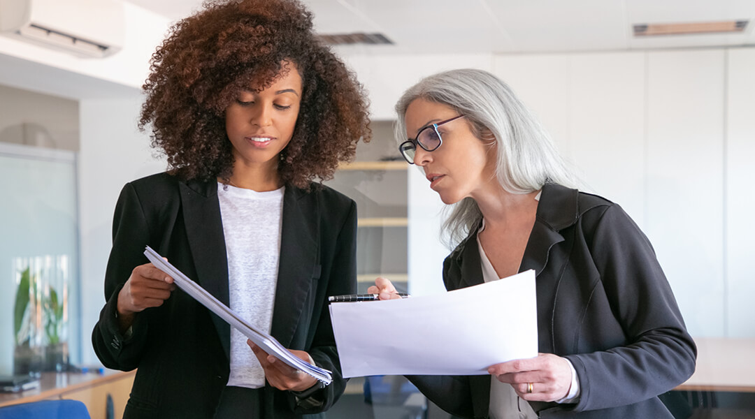 Two women in business suits discuss reports they are holding