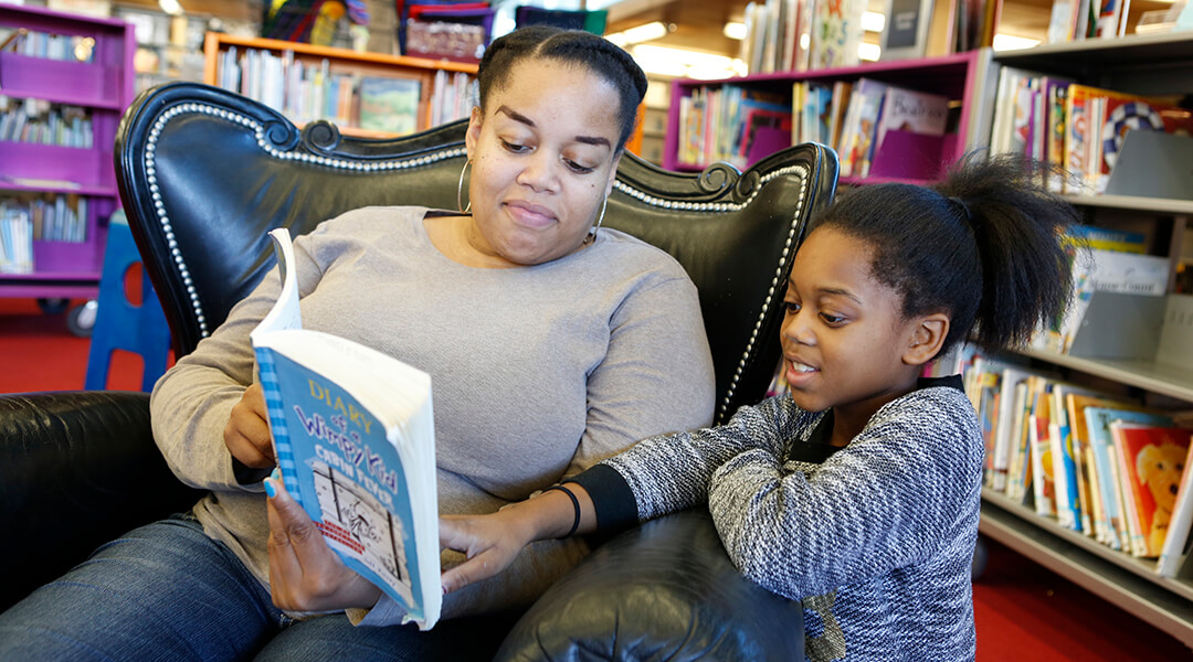 A mother sitting in a leather chair reading to her young daughter