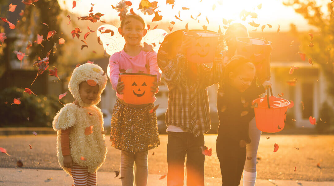 Five young children dressed in Halloween costumes going trick or treating