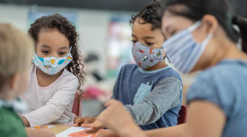 Three children wearing masks engaged in an art activity