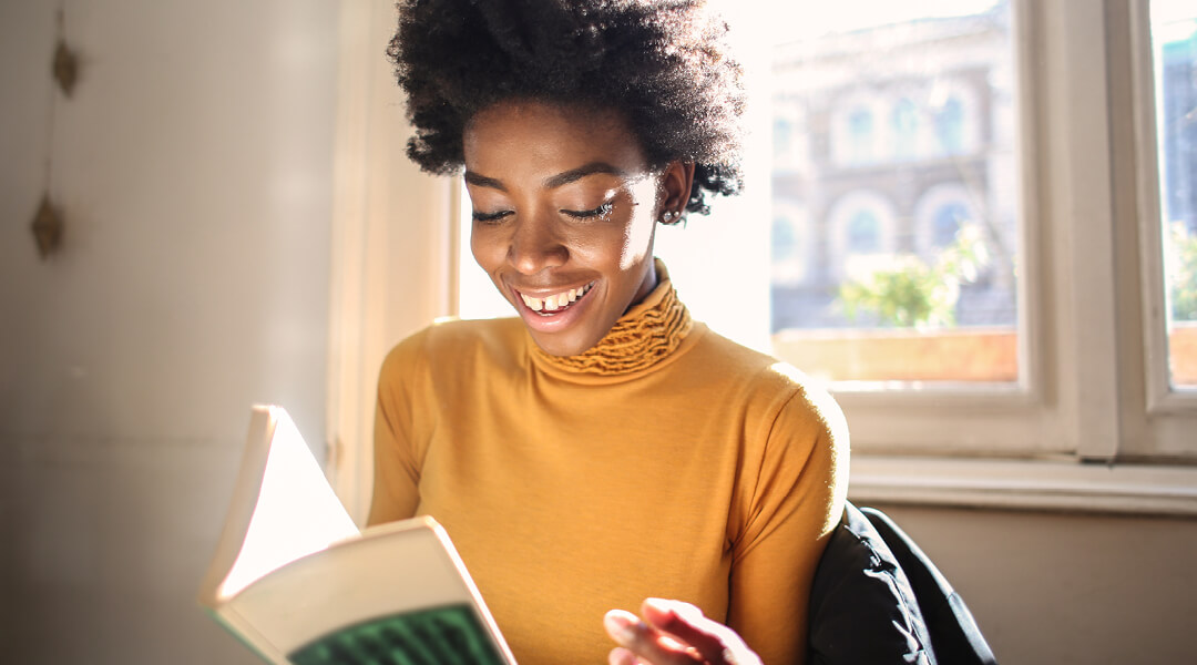 A smiling adult reading a book.